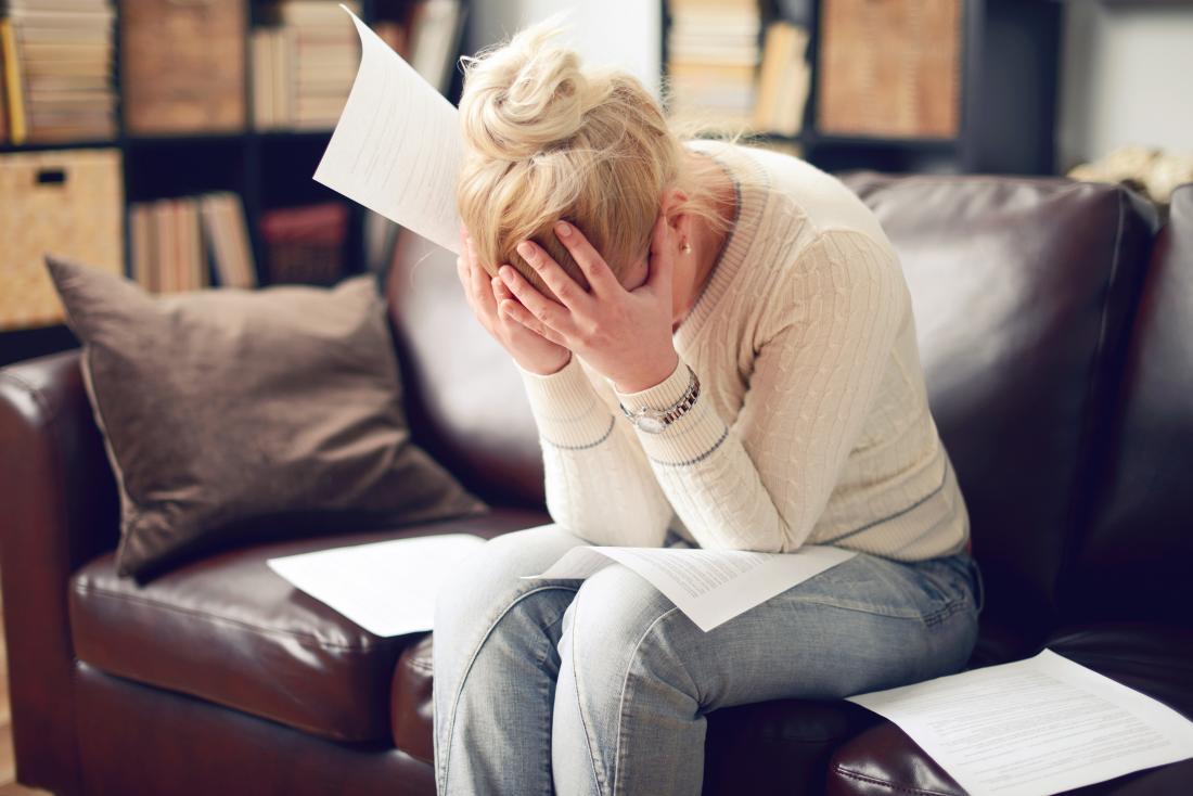 người phụ nữ với đầu trong tay bao quanh bởi giấy tờ
