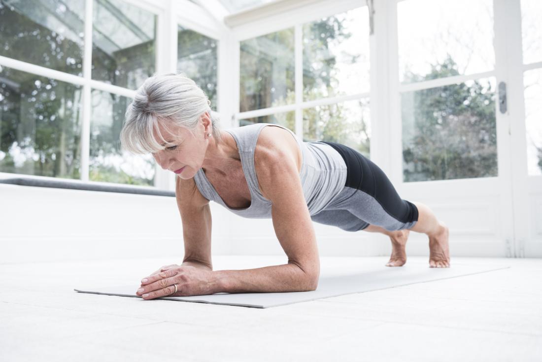 по-възрастна жена прави упражнение дъска