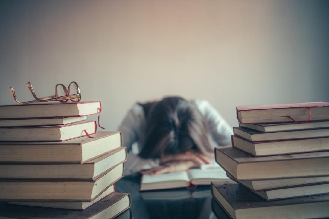 書籍で囲まれた女性の眠り