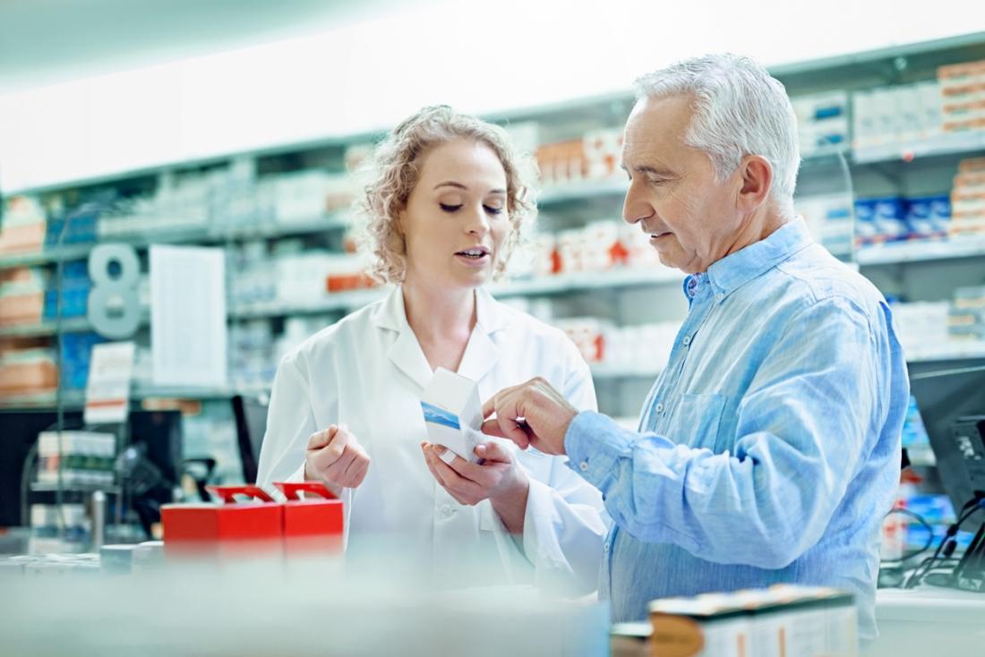 Apotheker, der Medizinverordnung mit Kunden bespricht.