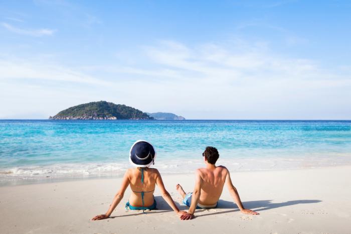 erkek ve kadın tropik sahilde kumda oturmak