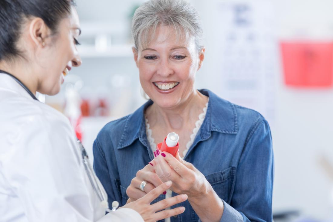 Kobieta omawia astmy inhalator z farmaceutą.