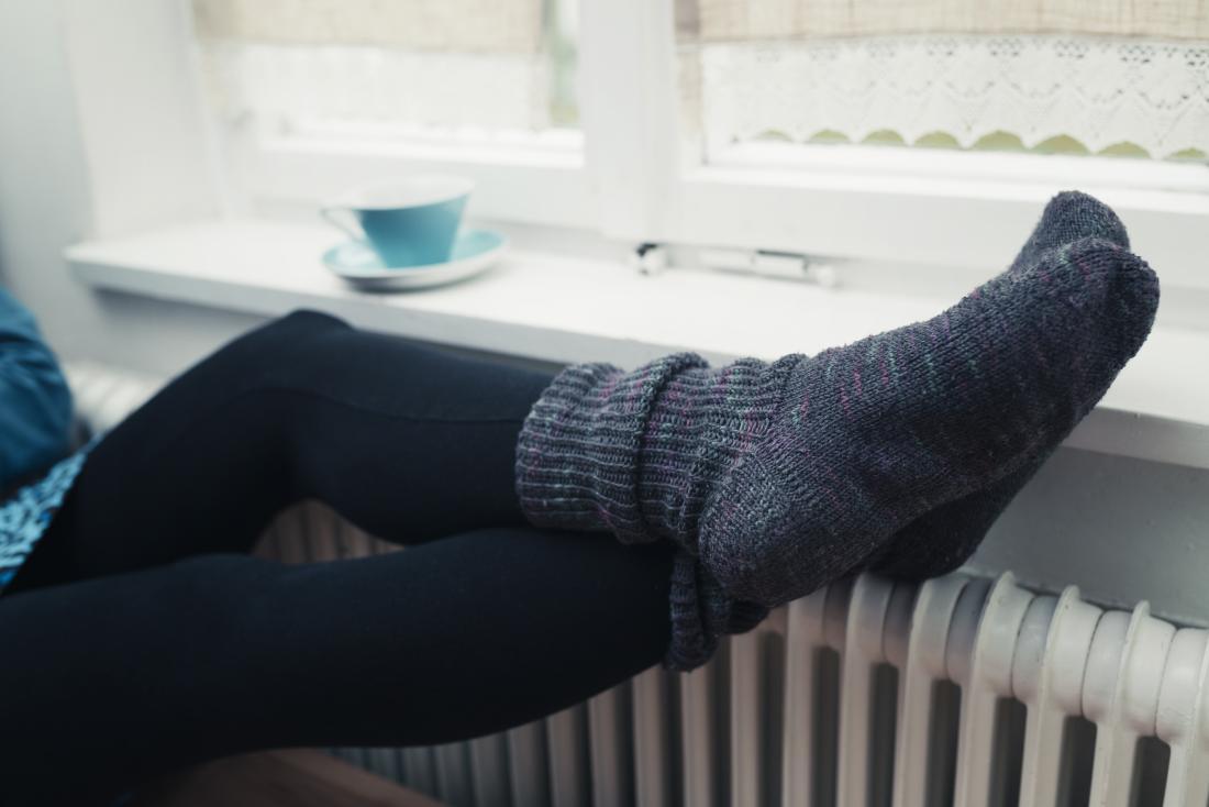 Persona con calzini invernali pesanti sui piedi freddi, appollaiato sopra la stufa del radiatore.