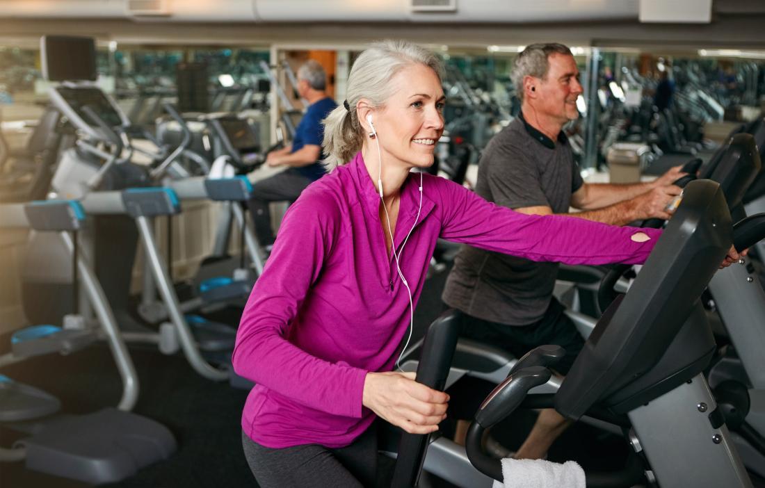 Mulher mais idosa no gym que exercita na máquina.