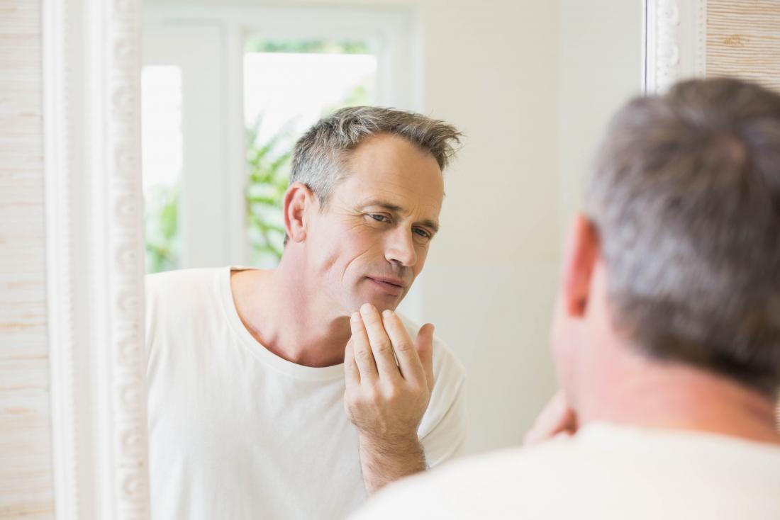 Reifer Mann, der im Spiegel untersucht Mund und Backen schaut.