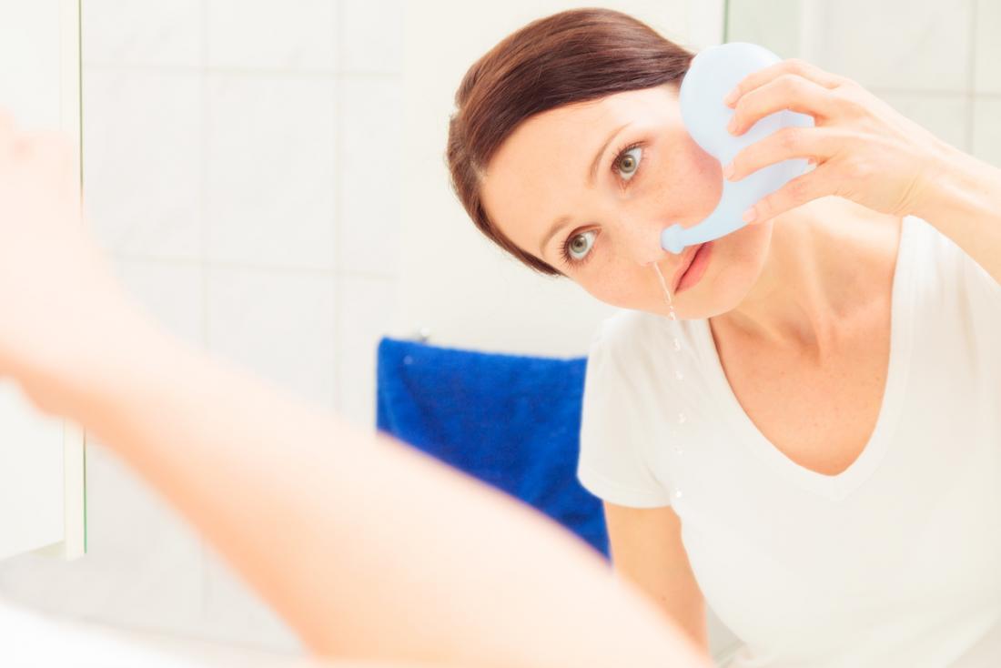 Mulher usando um pote de Neti para limpar o nariz de congestionamento.