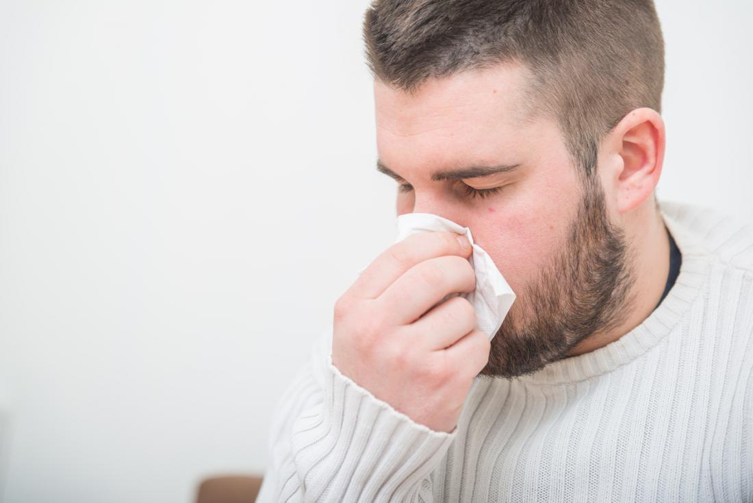 人はインフルエンザや風邪のために優しく鼻を吹いています。