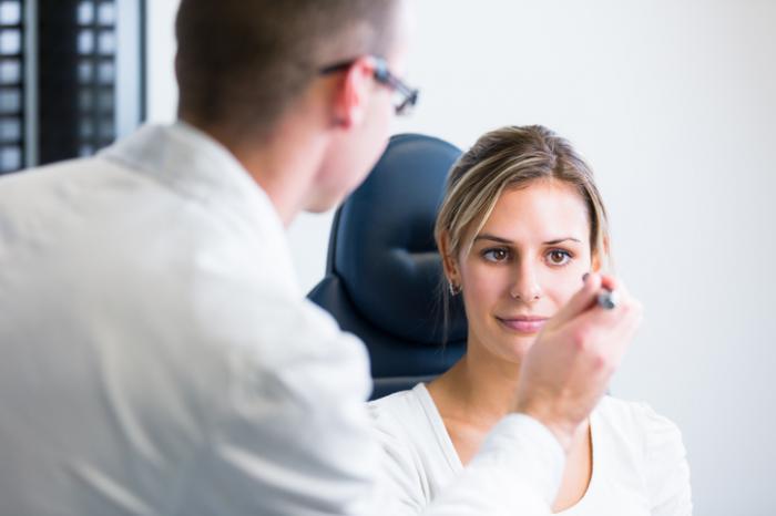 Um oftalmologista inspeciona os olhos de uma mulher.