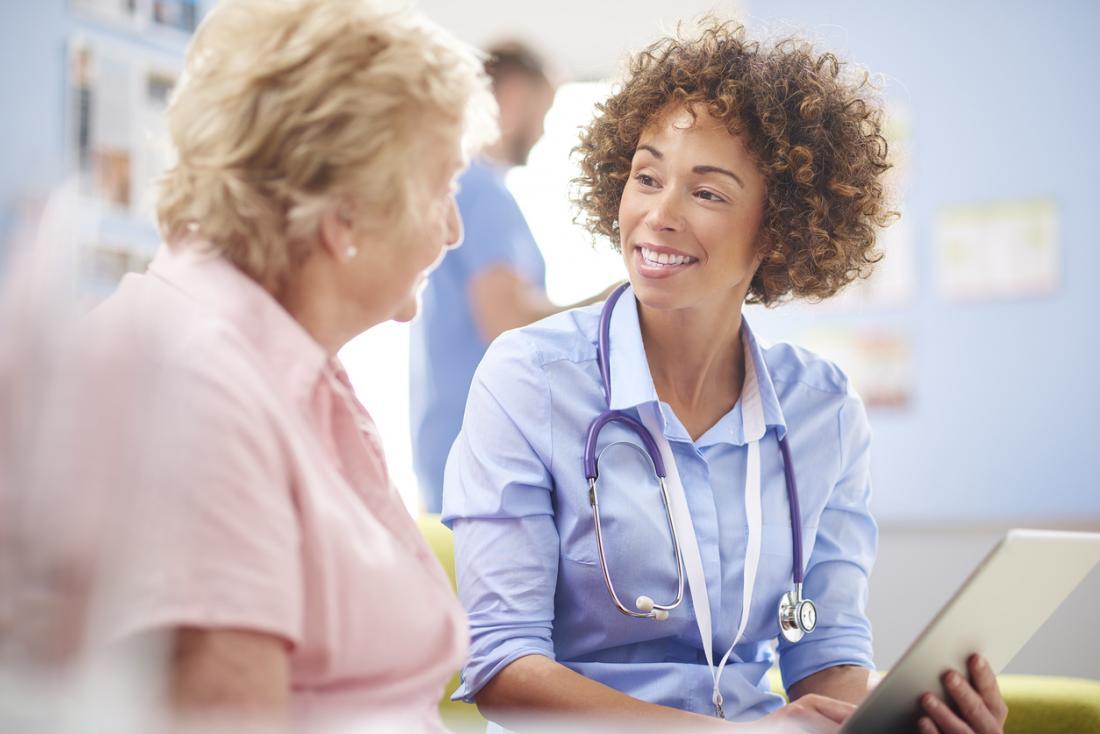 Junge Ärztin, die mit älterem weiblichem Patienten spricht.