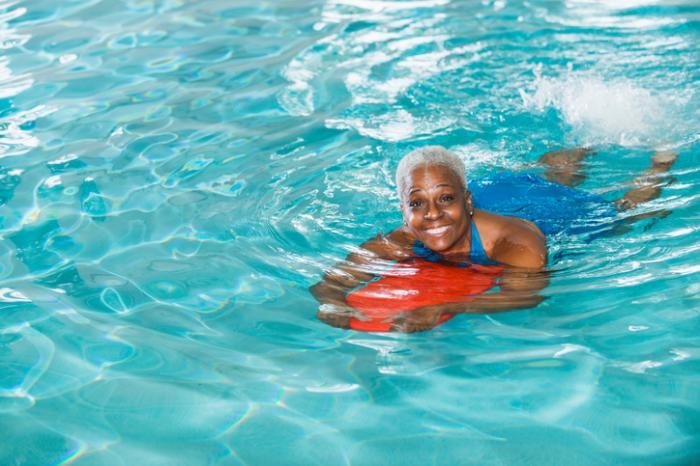 [uśmiechnięta szczęśliwa kobieta w średnim wieku pływanie w basenie]