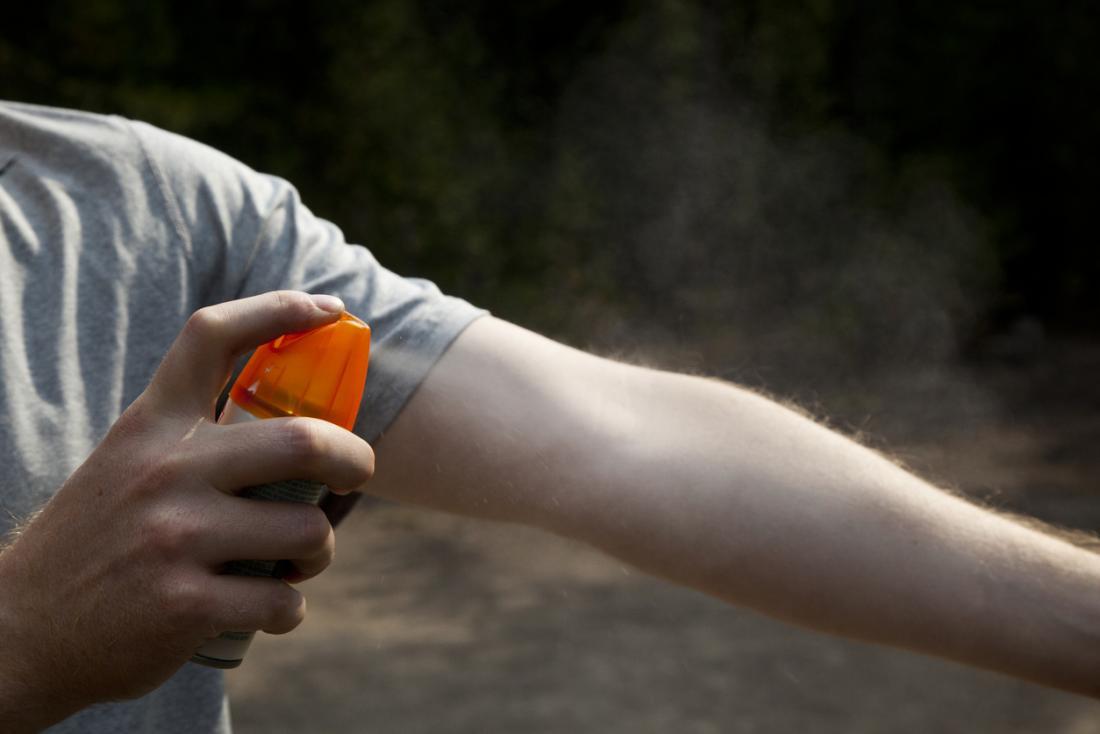 Uomo che spruzza repellente per zanzare sul suo avambraccio.