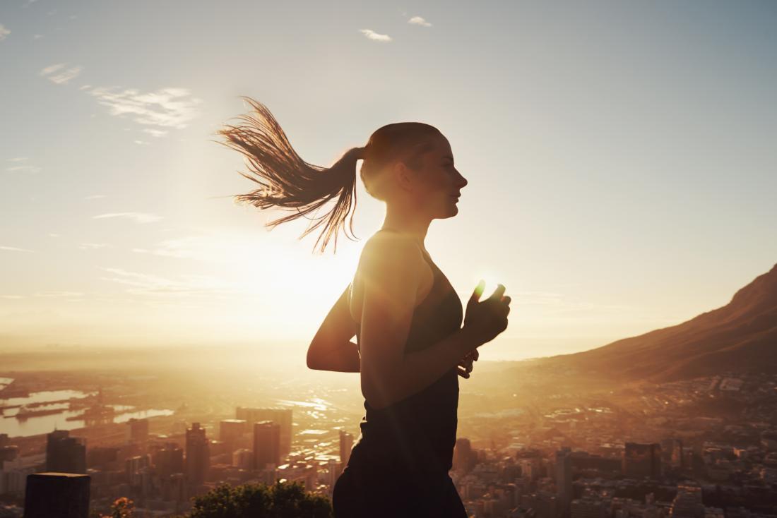 太陽の下で走っている女性