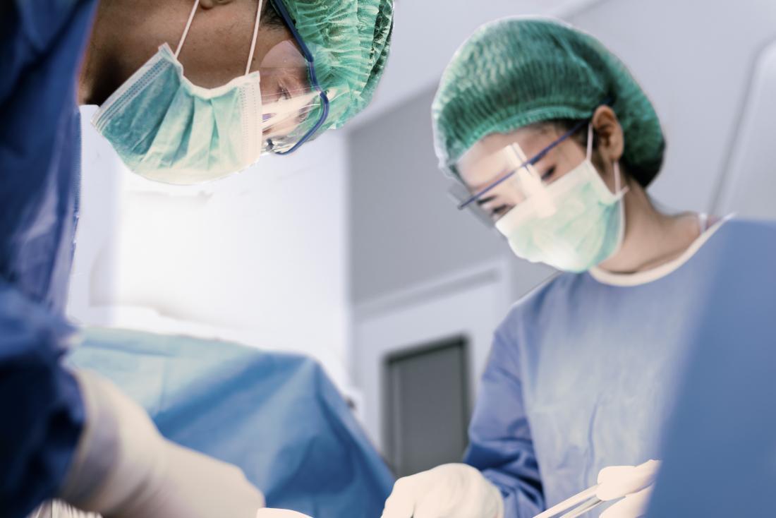 zwei Chirurgen bei der Arbeit im Operationssaal, der Gesichtschirurgie durchführt