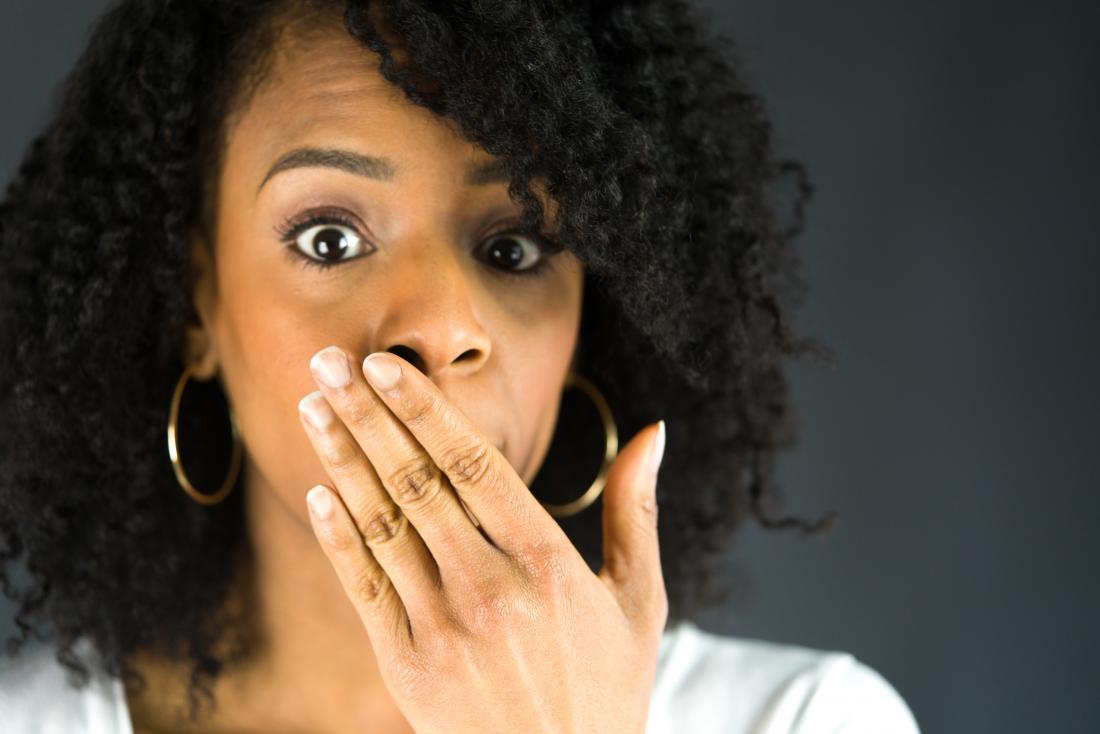 Frau, die ihren Mund mit einer Hand bedeckt