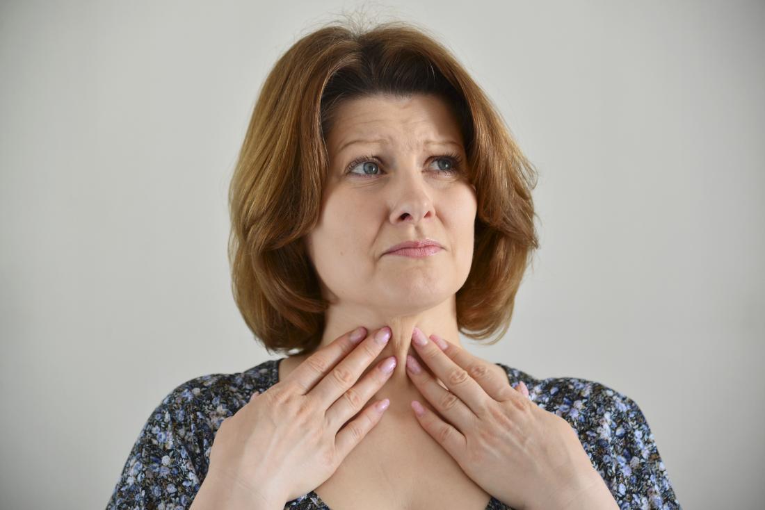 người phụ nữ chạm vào họng cô bằng cả hai tay
