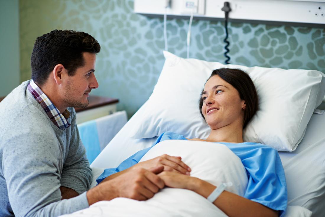 Mulher pré ou pós-operatório em leito hospitalar para cirurgia.