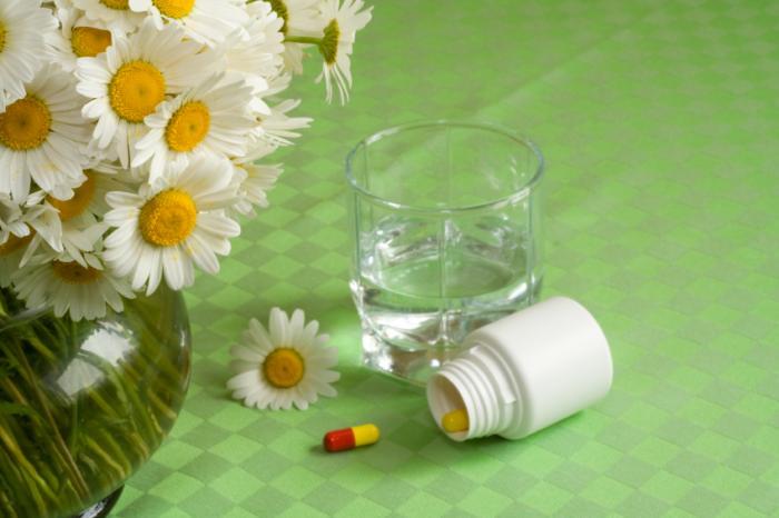 Pilules avec de l'eau et quelques fleurs.