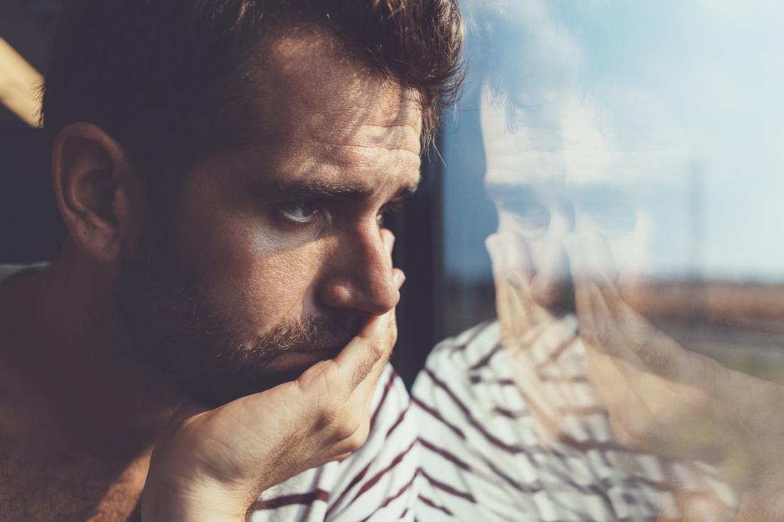 uomo triste guardando fuori da una finestra