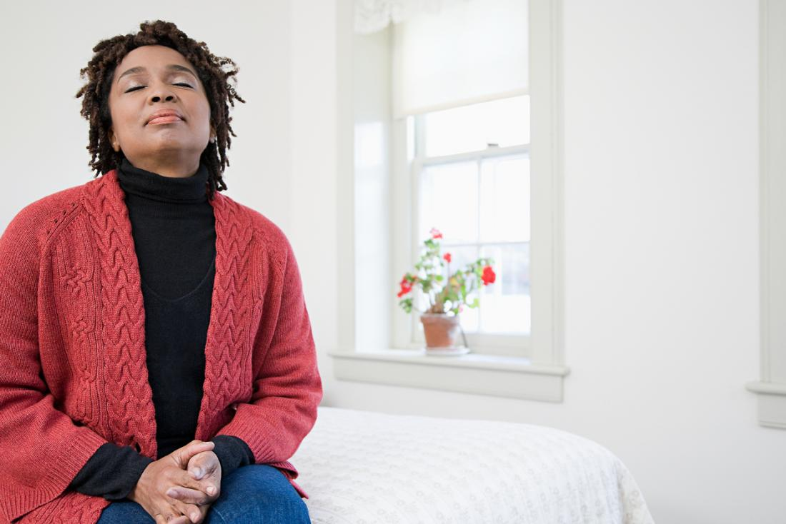 mulher calma respirando na cama dela