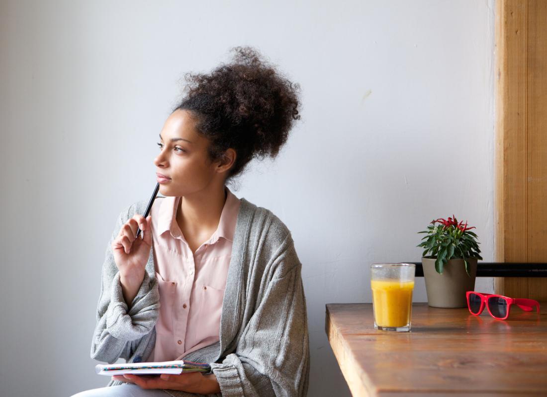 donna che pensa mentre si tiene un notebook