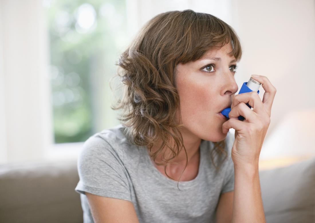 Donna con asma utilizzando l'inalatore.