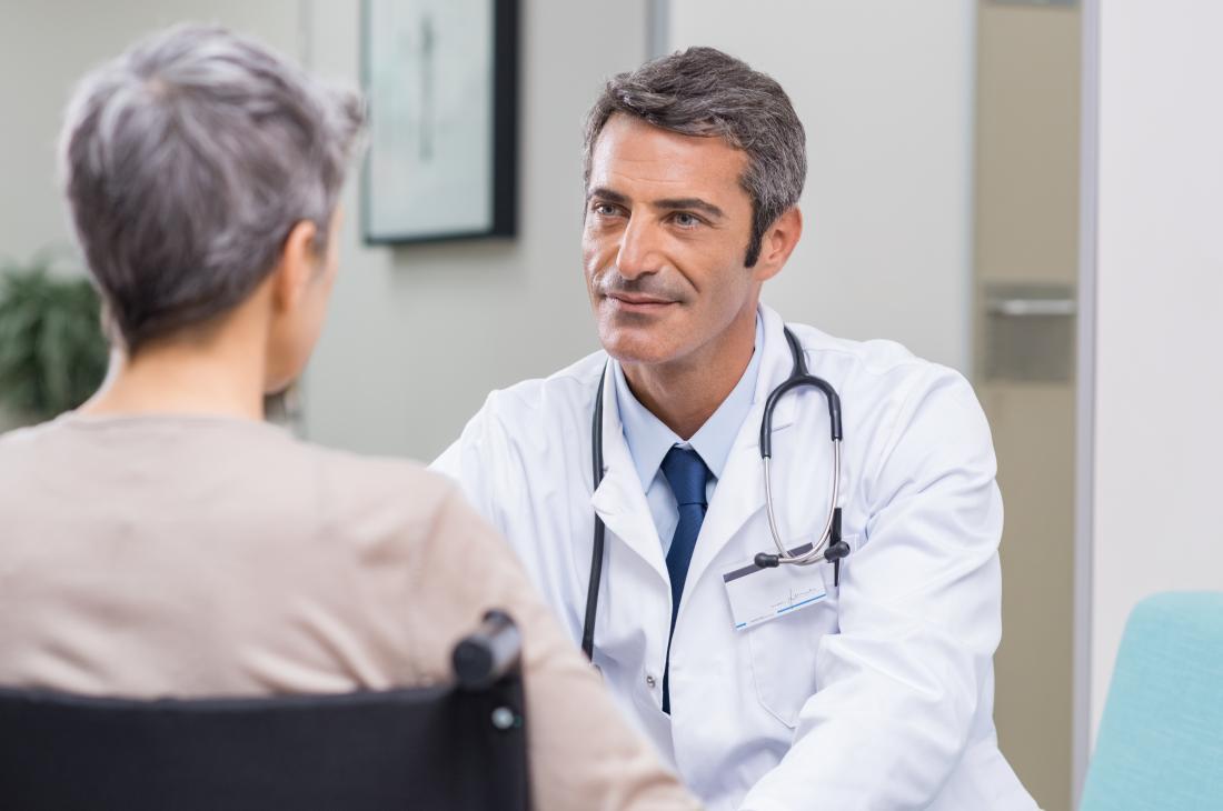 Doutor masculino que enfrenta o paciente obscurecido fêmea.