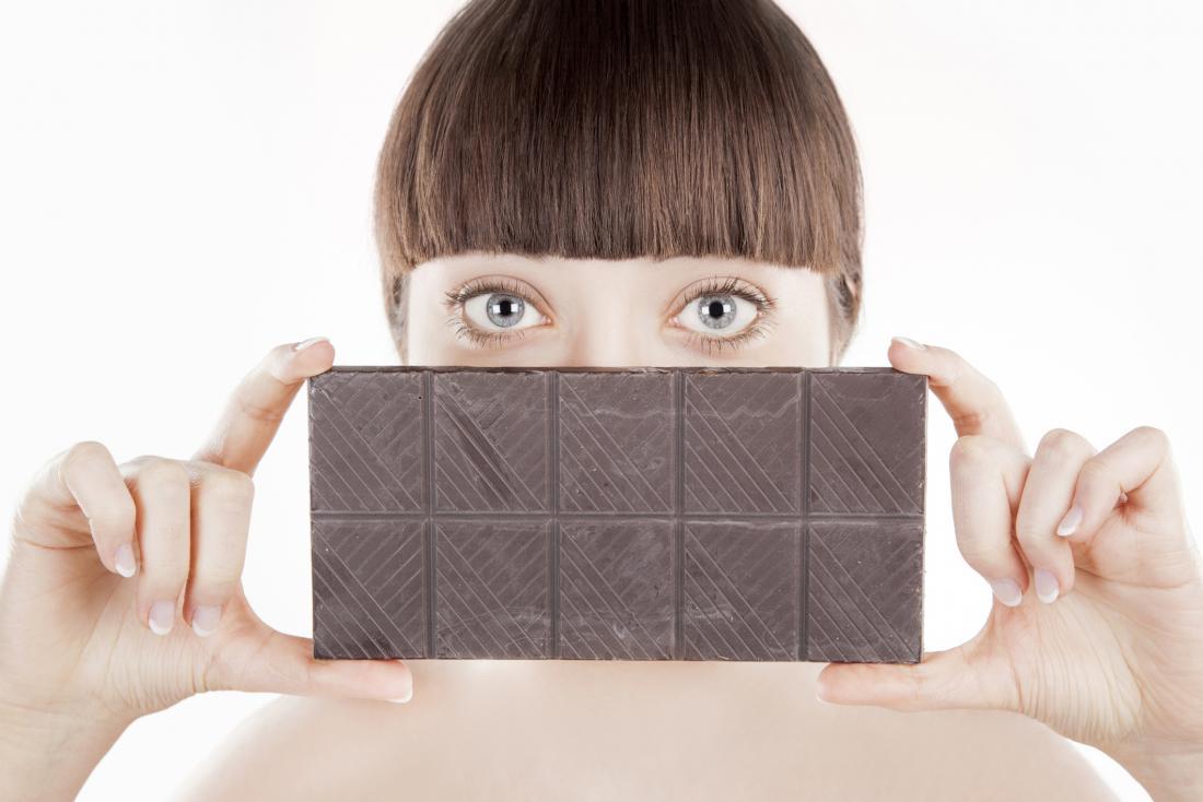 жена, държаща бар от тъмен шоколад
