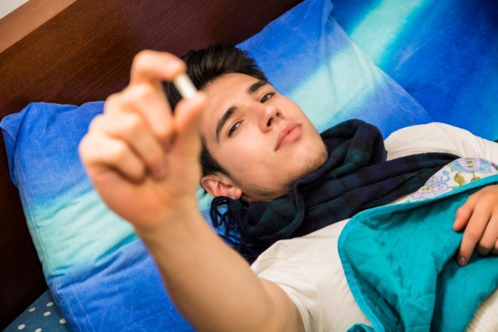 młody człowiek w łóżku trzyma leki depresji