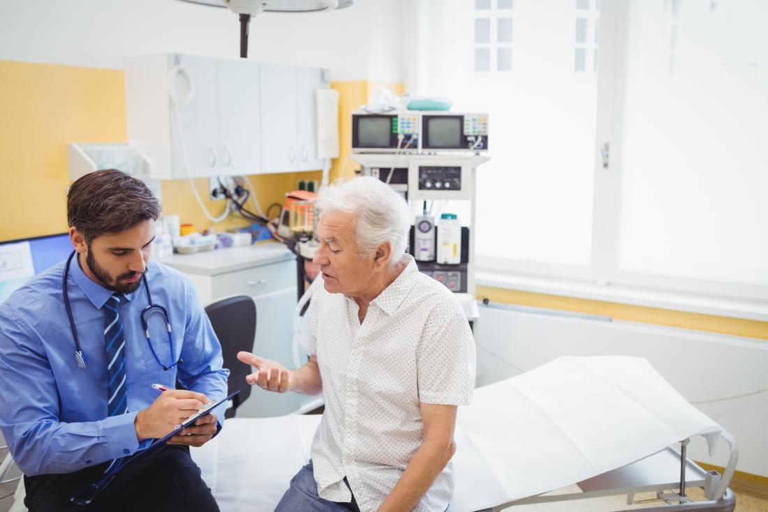 Bệnh nhân nam cao cấp với bác sĩ nam trẻ ngồi trên giường bệnh giải thích vấn đề.