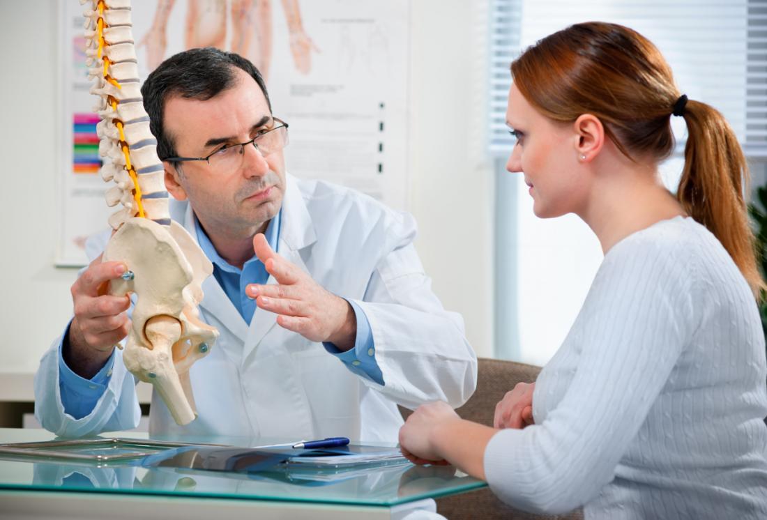 [лекар, който обяснява използването на модел на бедрата и гръбначния стълб]
