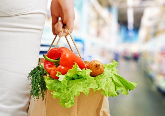 女性が野菜の袋を運んでいる。