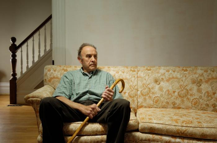 Un uomo più anziano si siede da solo nella sua casa