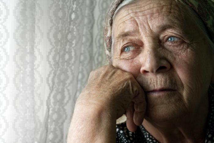 Una signora anziana guarda pensierosa fuori da una finestra