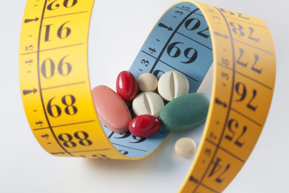 Perdita di peso e pillole per la dieta circondate da nastro di misurazione.