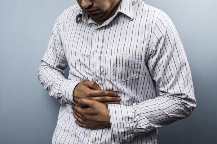 男は胃を不快にしている。
