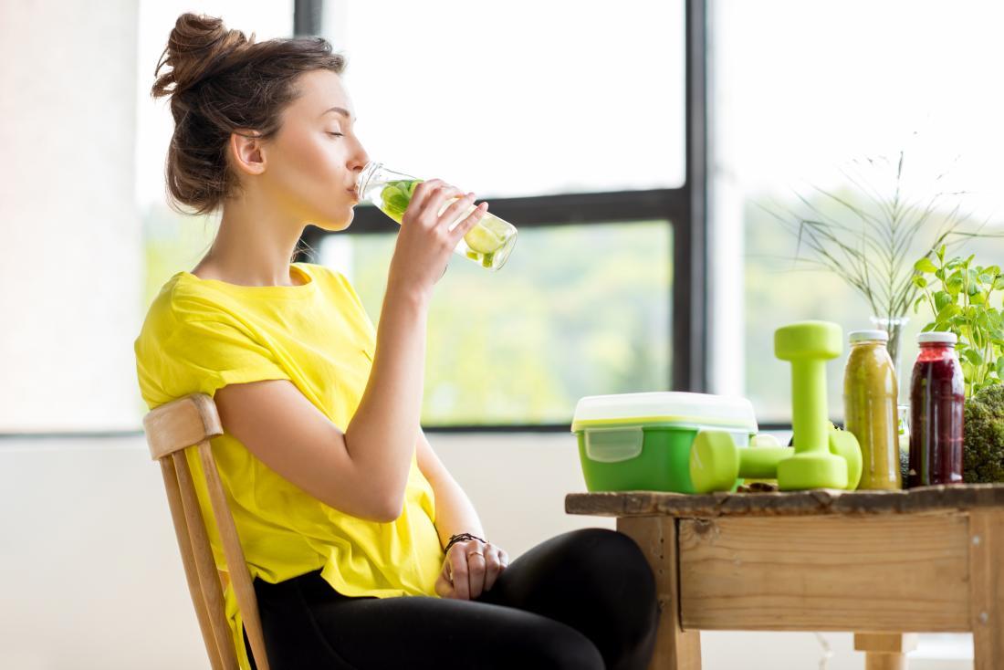 Fitness spor giysiler masada masada oturan kadın, suyu ve limon suyu temizliği ile masada halter ağırlık.