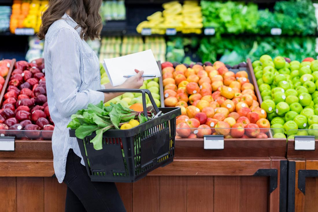 Kadın bakkal meyve ve sebze üretim bölümünde bakarak bakkal alışveriş.