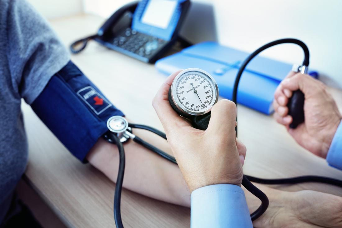 ein Arzt, der den Blutdruck eines Patienten misst