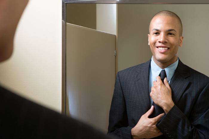 Một người đàn ông điều chỉnh cà vạt mỉm cười trong gương