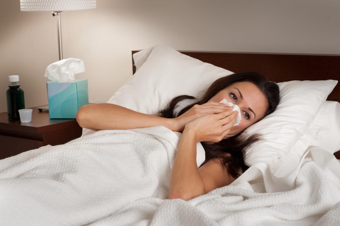 người phụ nữ bị lạnh nằm trên giường đang thổi mũi