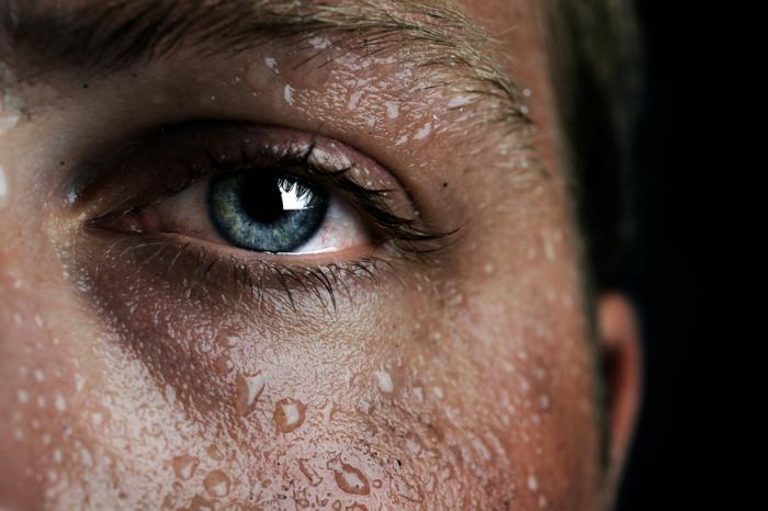 Schließen Sie oben von einem bemannten Auge, das durch Schweiß umgeben wird