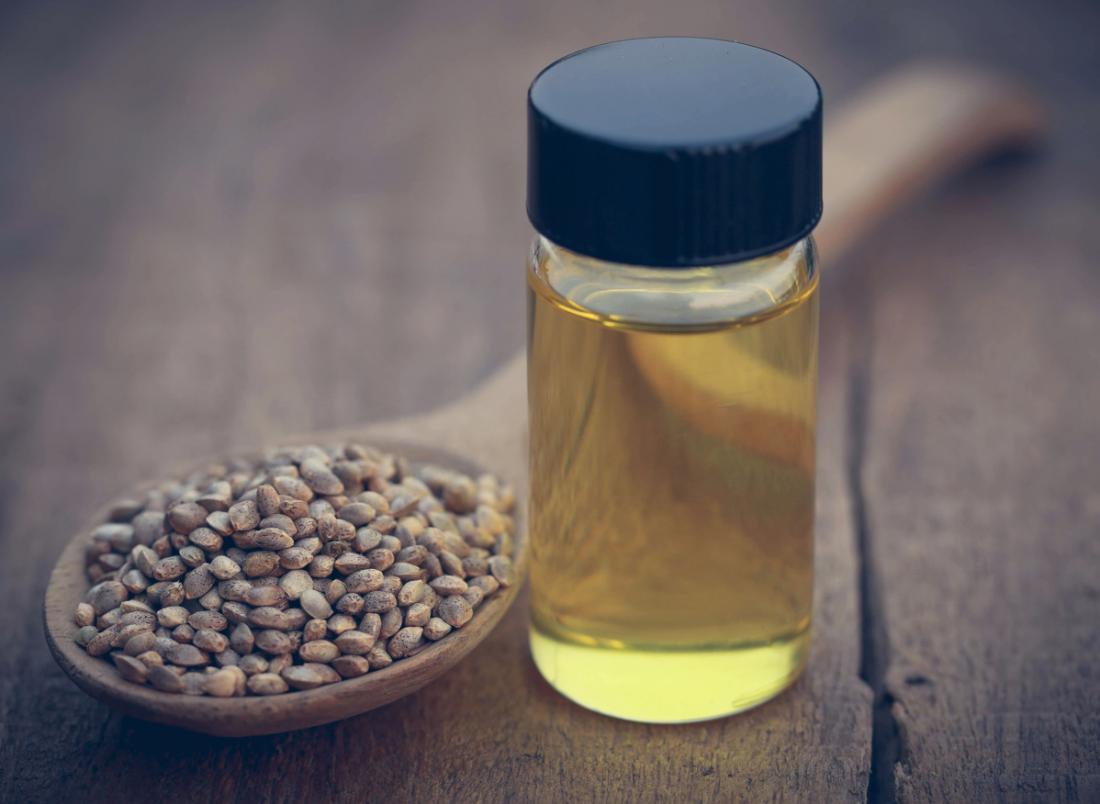 Bir şişede CBD yağı, kenevir tohumu ile dolu bir tahta kaşık yanında.