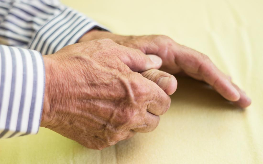 Yaşlı adamın eli, bir yandan artrit ağrısı nedeniyle diğerinin başparmağını tutan.