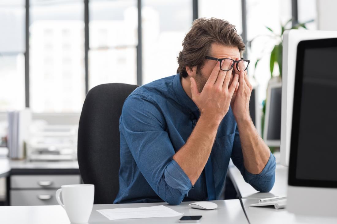 Baş ağrısı ve yorgunluk nedeniyle gözleri ovuşturarak yorgun iş adamı.