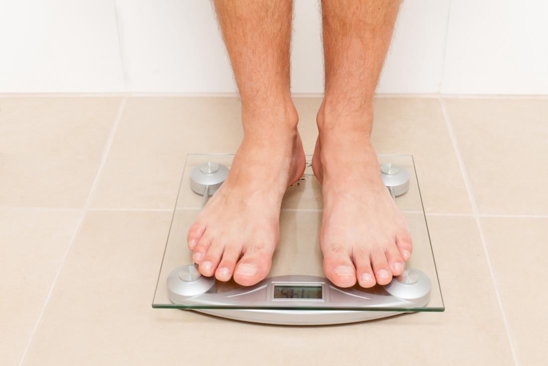 Człowiek stojący na wadze.