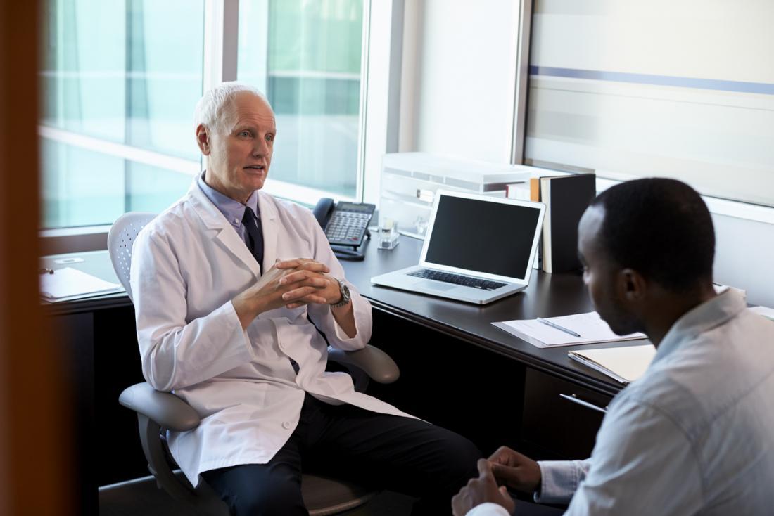 Älterer weißer männlicher Doktor mit jungem schwarzem männlichem Patienten, in der Diskussion.