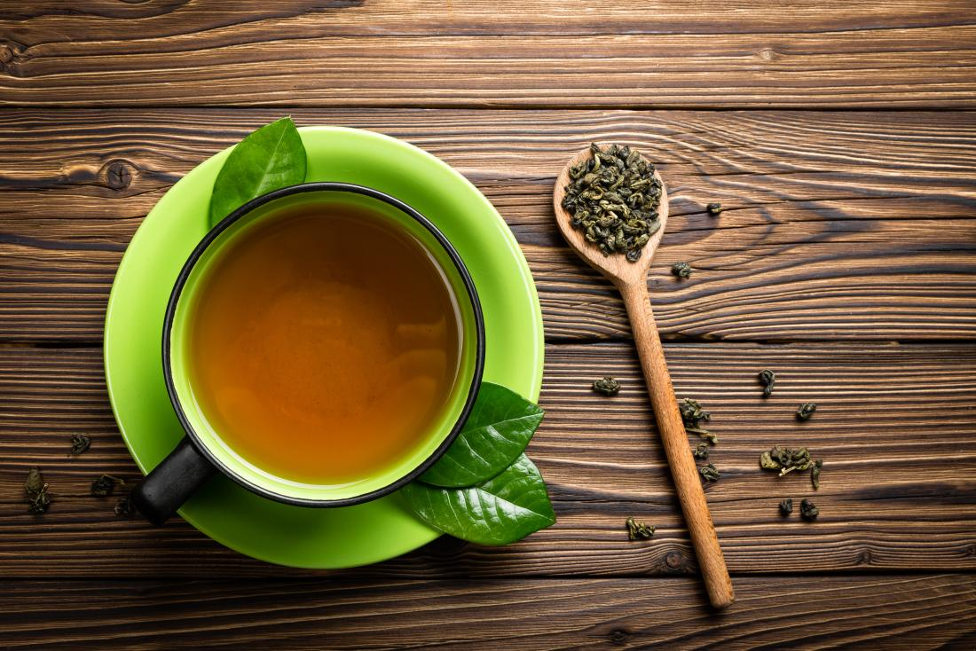 Grüner Tee in der Schale mit Teeblättern auf hölzernem Löffel.