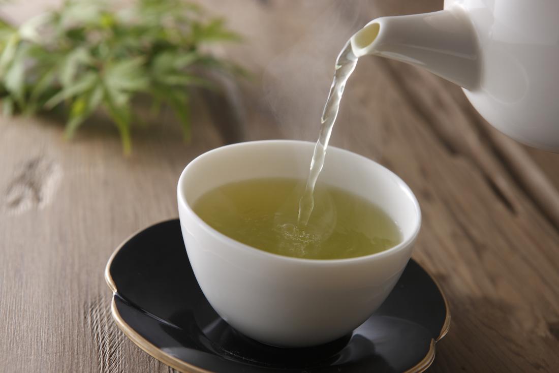 Grüner Kräutertee, der von der Teekanne in Schale gegossen wird.