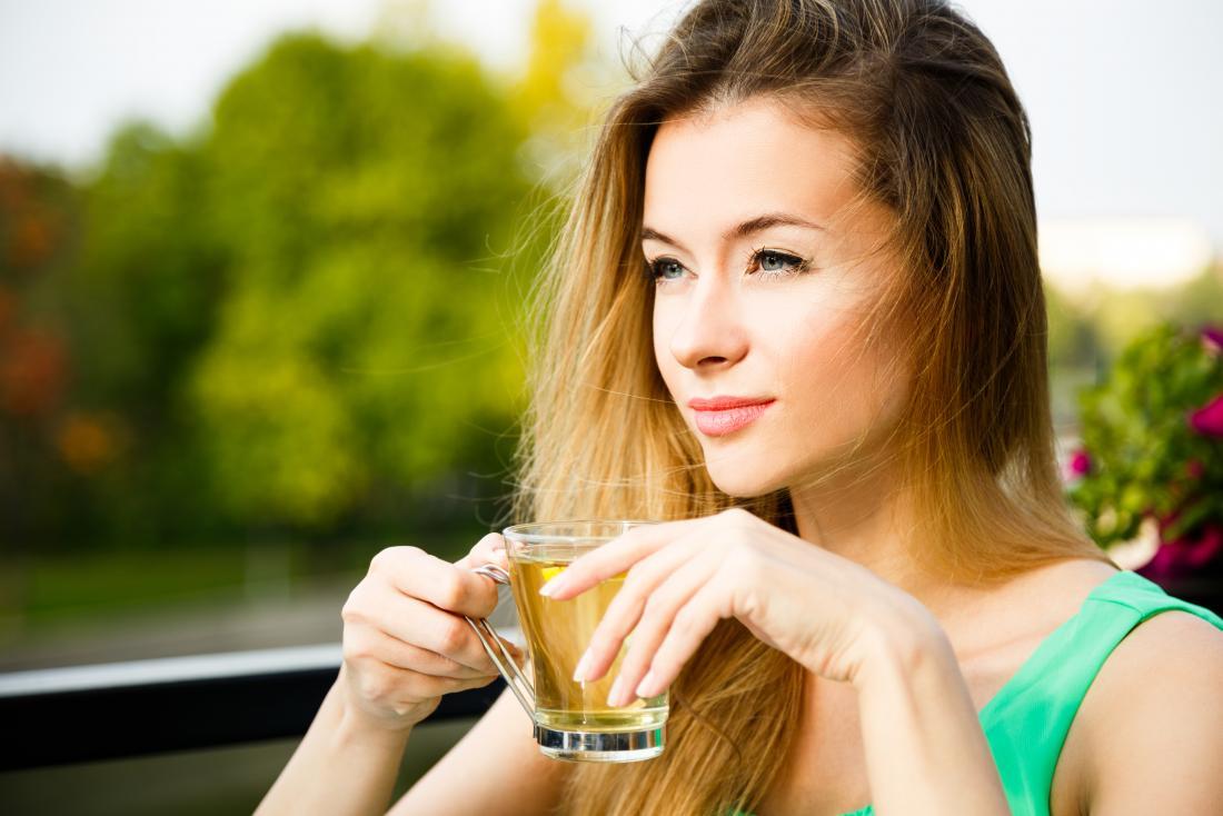 Frau draußen, grünen Kräutertee trinkend.