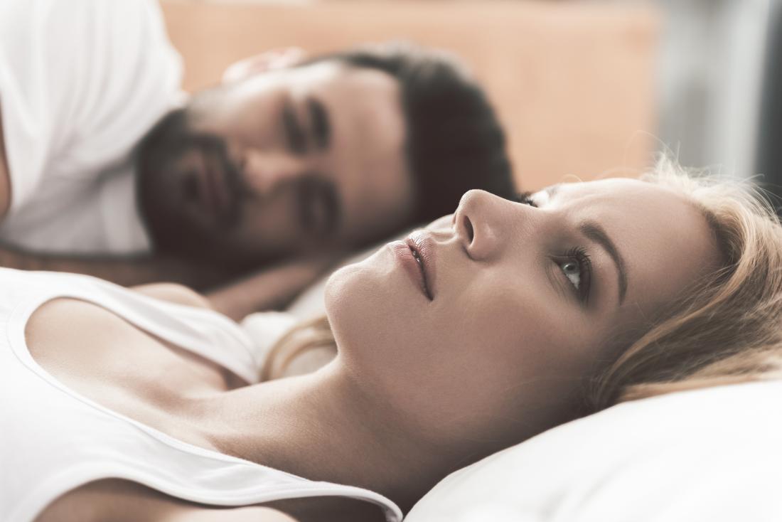 mulher acordada na cama ao lado do parceiro se preocupar com sexo após histerectomia